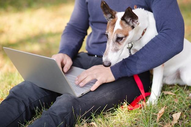 Cão com dono e laptop no parque