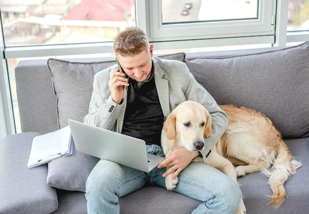 Cão de carinho bonito homem enquanto trabalhava