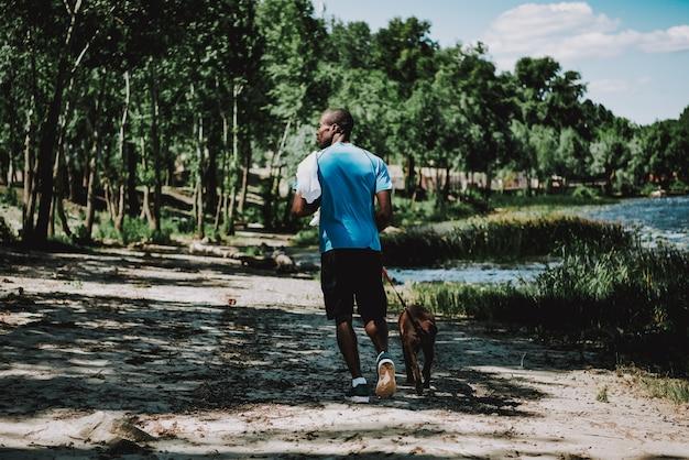 Cão de passeio do homem do americano africano pelo rio.
