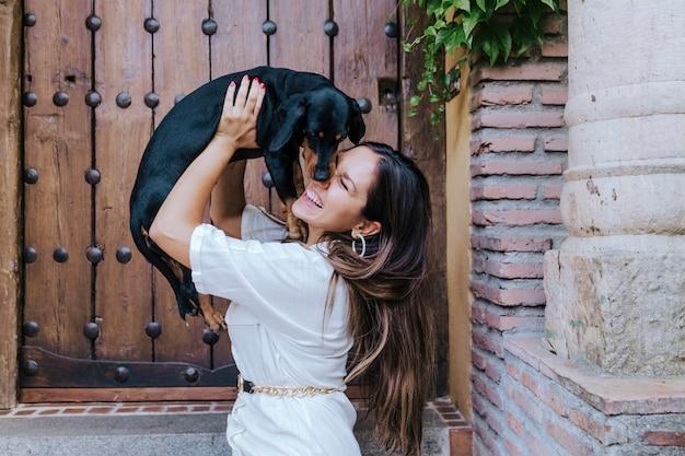 Cão de salsicha pequeno bonito que senta-se ao ar livre com seu proprietário em casa. adorável cão beijando dono. amor pelo conceito de animais