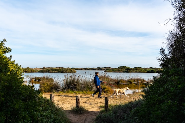 Cão e seu dono passeando ao longo do lago gavines, perto de uma praia em valência.