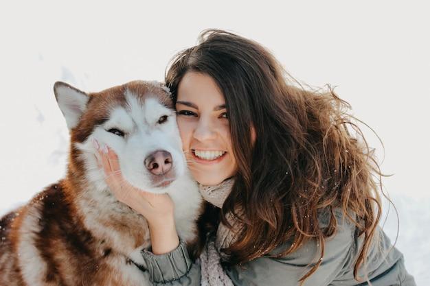 Cão husky vermelho com sua amante menina morena na floresta ao ar livre na estação fria