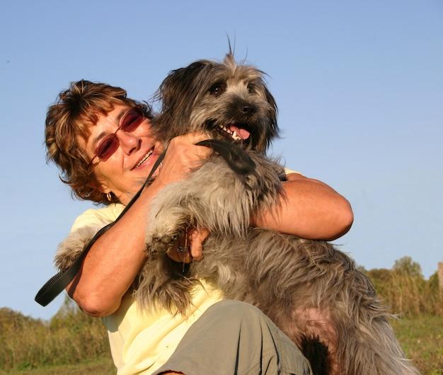 Cão pastor dos pirinéus e mulher sênior