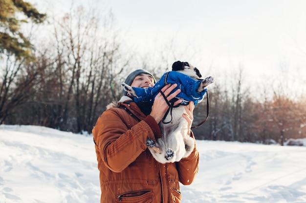 Cão pug andando com seu mestre. homem brincando com seu animal de estimação e se divertindo. filhote de cachorro vestindo casaco de inverno.