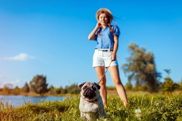 Cão pug sentado ao rio. cachorrinho feliz que espera um comando do mestre. cão e mulher relaxando ao ar livre
