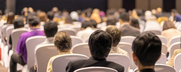 Capa da faixa de visão traseira do público ouvindo os palestrantes no palco na sala de conferências ou na reunião do seminário, negócios e educação sobre investimentos