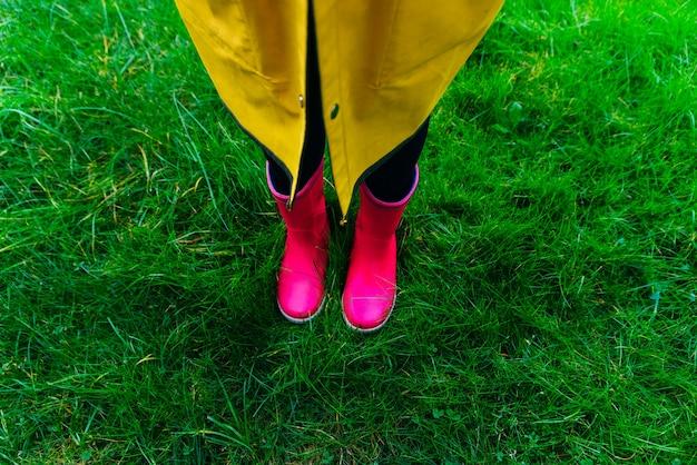 Capa de chuva amarela e botas de borracha rosa na grama verde