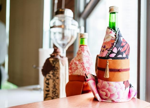 Capa de embalagem para garrafa de saquê japonês com estilo quimono japonês no balcão de sushi da omakase