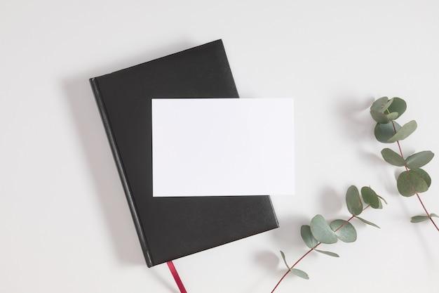 Capa de livro preta com cartão em branco e folhas de eucalipto em fundo cinza