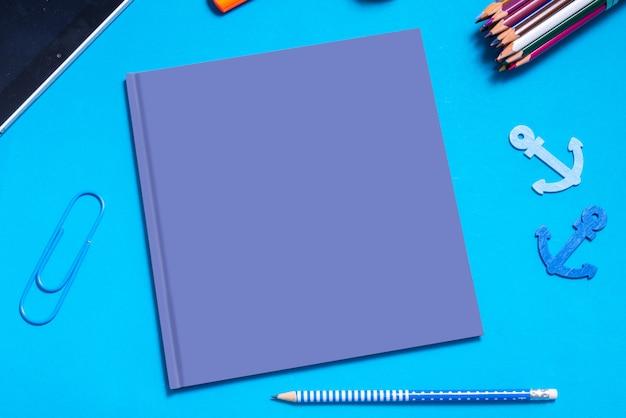 Capa de livro vazio azul simulado acima, em cima da mesa com estacionário