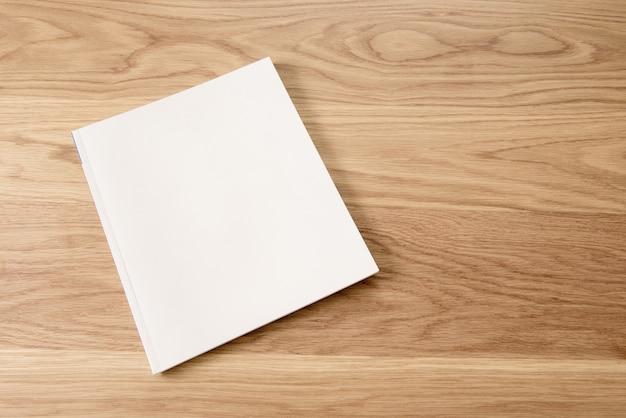 Capa de revista branca em branco sobre fundo de mesa de madeira.