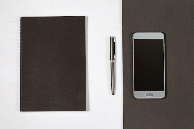 Capa preta de caderno fechado e caneta de prata. vista do topo