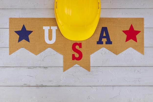 Capacete amarelo de construção no feliz dia do trabalho dos eua patriótico um feriado federal dos estados unidos da américa