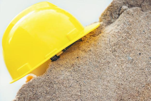 Capacete amarelo e casa modelo de madeira em uma pilha de areia