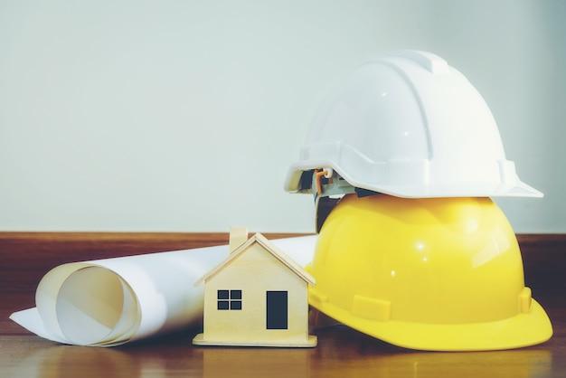 Capacete branco e amarelo com casas de madeira e vários dispositivos que são colocados em um assoalho de madeira.