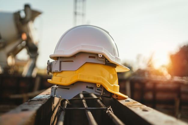 Capacete branco e amarelo em aço no canteiro de obras