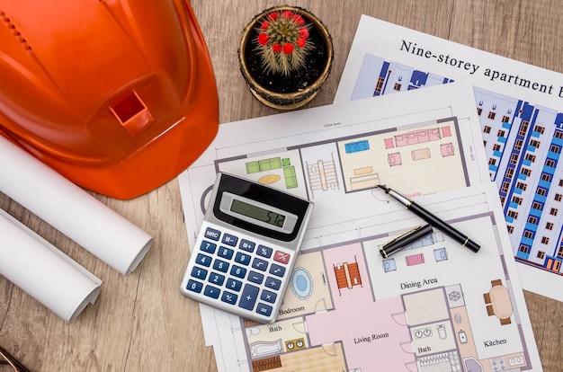 Capacete com projetos e réguas, caneta e calculadora na mesa