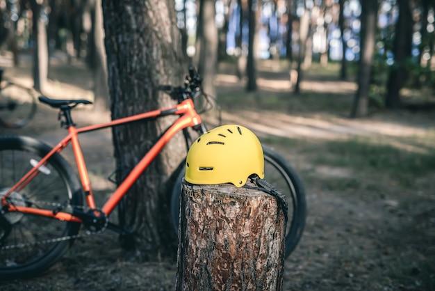 Capacete de bicicleta no toco e bicicleta na floresta de pinheiros