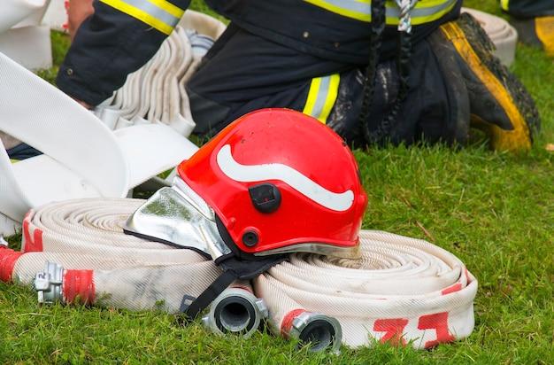 Capacete de bombeiro sobre uma mangueira na grama