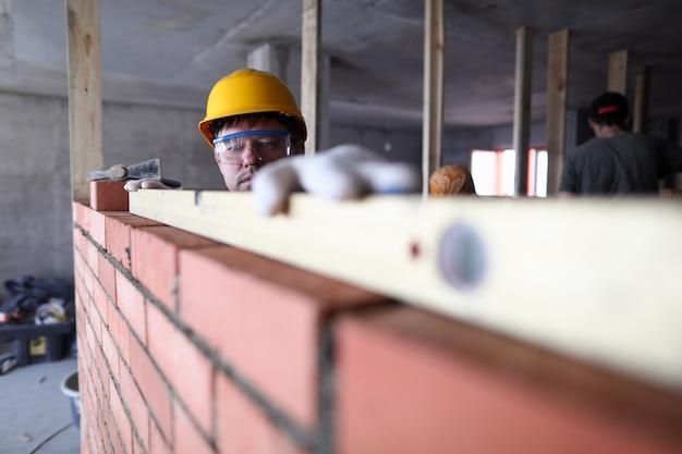 Capacete de cara de construção mede alvenaria de nível