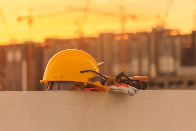 Capacete de construção e ferramentas de construção no canteiro de obras