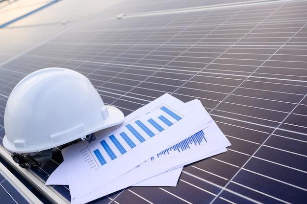 Capacete de engenheiro de segurança em instalações industriais onde os painéis solares são instalados usando energia solar primeiro conceito de plano de fundo de estação de energia solar.