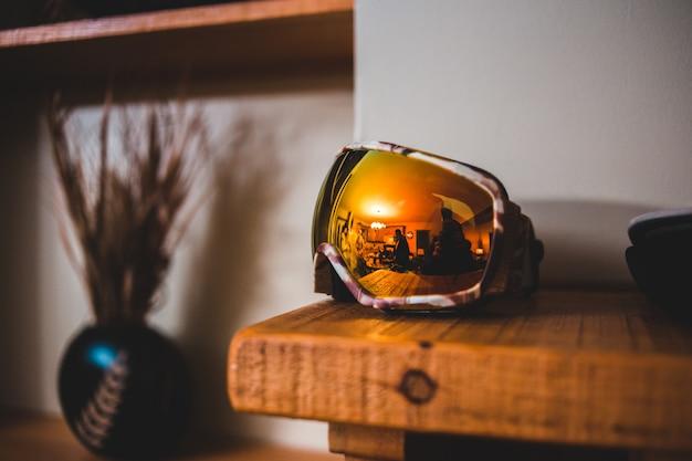 Capacete de motociclista preto e amarelo na mesa de madeira marrom