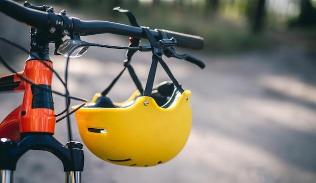 Capacete de proteção pendurado no guidão de bicicleta, close-up