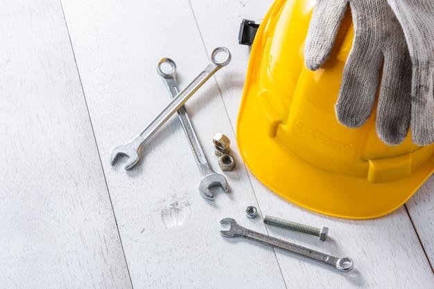 Capacete de segurança amarelo e ferramentas na mesa de madeira branca