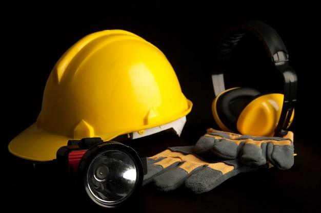 Capacete de segurança amarelo, luva de couro, lâmpada principal, auscultadores no fundo preto.