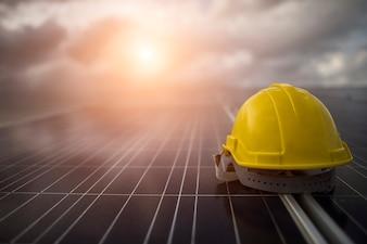 Capacete de segurança amarelo no painel da célula solar