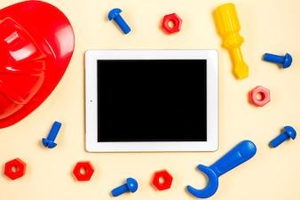 Capacete de segurança colorido; parafusos; parafusos; chave de fenda e chave de fenda ao redor do tablet digital
