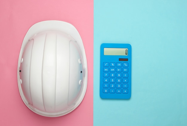 Capacete de segurança de construção de engenharia e calculadora em pastel bluepink. cálculo do custo de reparo ou construção de uma casa. postura plana