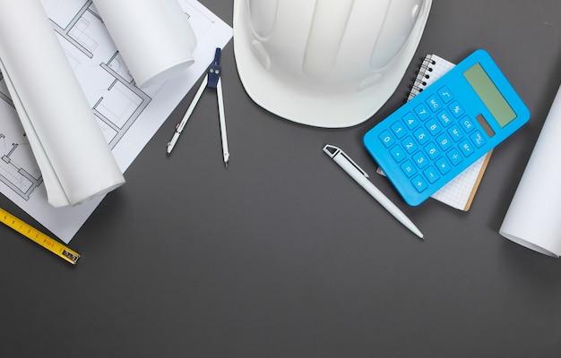 Capacete de segurança de construção de engenharia, rolos de planta, plano de projeto e calculadora em cinza