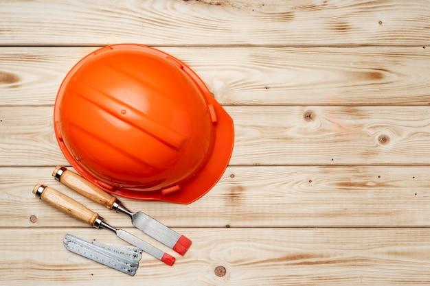 Capacete de segurança de ferramentas de trabalhador da construção civil e cinzel na vista superior do fundo de madeira