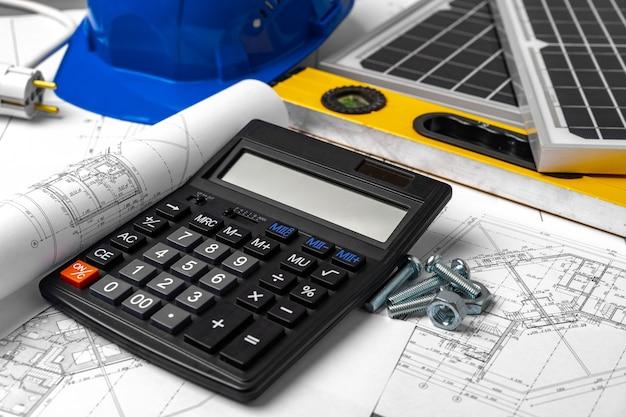 Capacete de segurança de plantas de construção e bateria solar na mesa do arquiteto