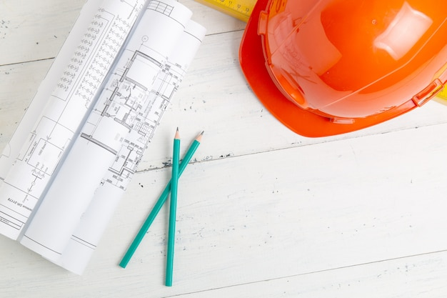 Capacete de segurança, desenhos em papel e lápis. o trabalho de um engenheiro civil.
