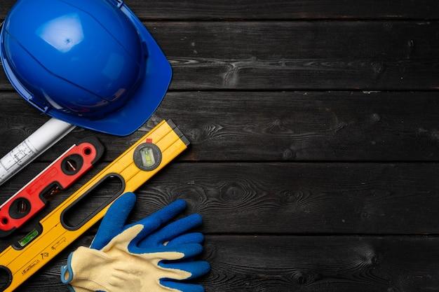 Capacete de segurança e luvas de trabalhador da construção civil na vista superior da superfície de madeira