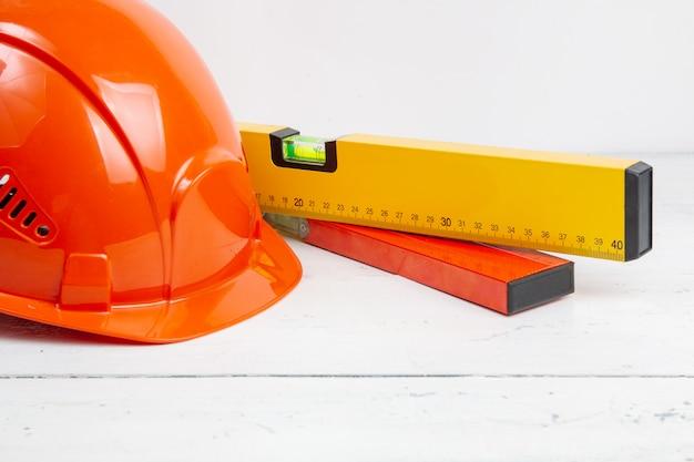Capacete de segurança e nível de construção em uma mesa branca
