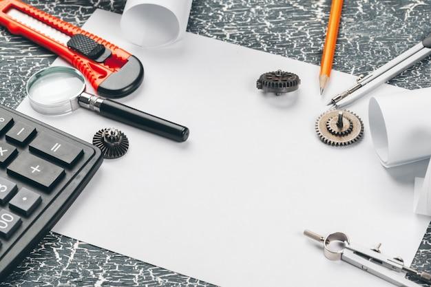 Capacete de segurança e pergaminhos de desenhos e suprimentos de engenharia