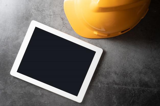 Capacete de segurança e tablet com palavras de saúde e segurança no local de trabalho