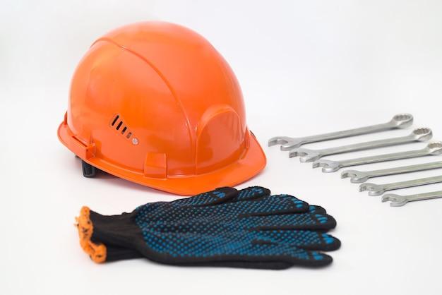 Capacete de segurança laranja, luvas de trabalho e chaves em um fundo branco.