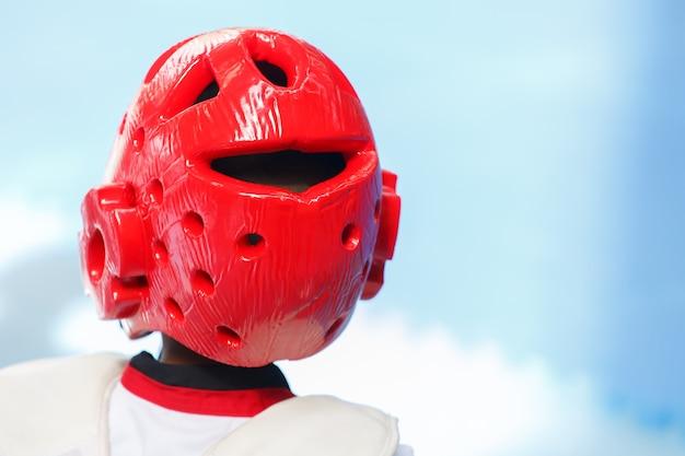 Capacete de teakwondo vermelho brilhante na cabeça da criança