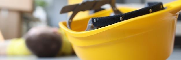 Capacete de trabalhador amarelo no chão ao lado de um trabalhador da construção civil imóvel