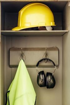 Capacete de visão frontal e fones de ouvido pendurados em um armário