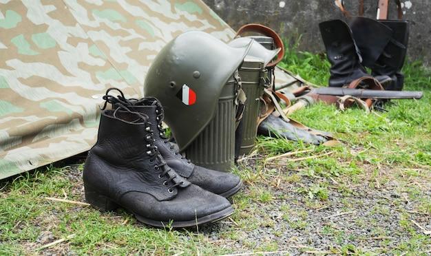 Capacete do exército alemão e botas período da segunda guerra mundial, ao ar livre