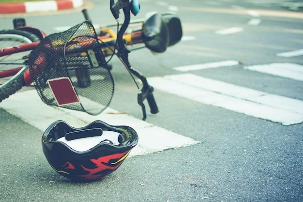 Capacete e bicicleta caídos na estrada em uma faixa de pedestres, após acidente