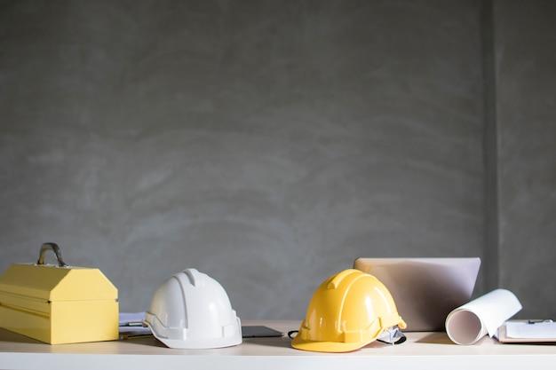 Capacete e ferramenta de construção na mesa