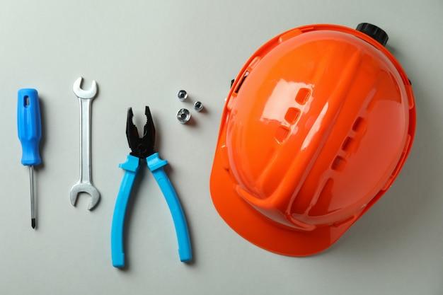 Capacete e ferramentas de trabalho em cinza claro