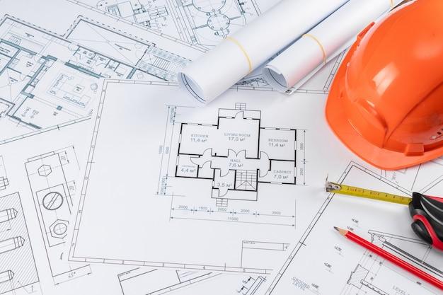 Capacete laranja, lápis, desenhos de construção arquitetônica, fita métrica